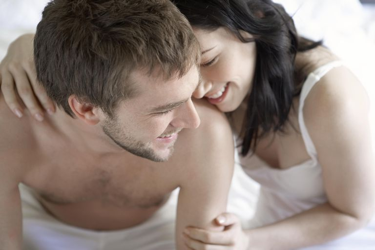 Young couple sitting on bed, smiling, close-up, about to have sex while taking Clomid