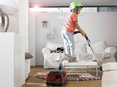 Boy in living room using vacuum cleaner