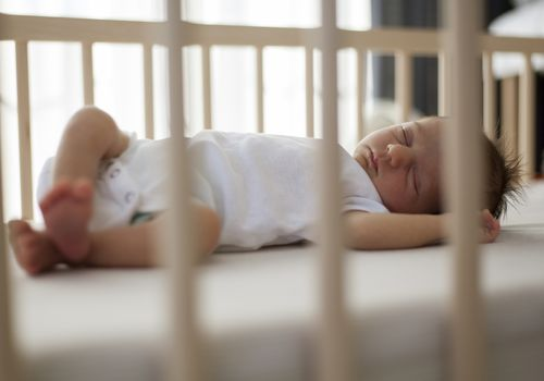 infant sleeping in a crib