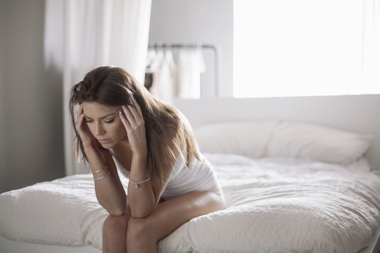Young woman sitting on edge of bed, holding head, wondering what causes infertility
