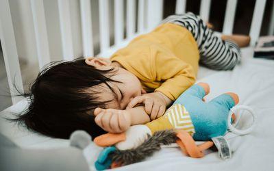 Thumb-sucking toddler sleeps in crib next to plush toy