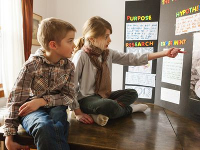 Two young kids looking at science project poster board