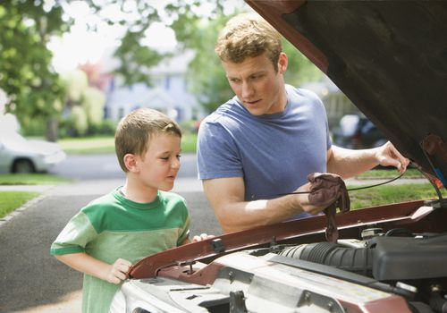 boy watching father repair car