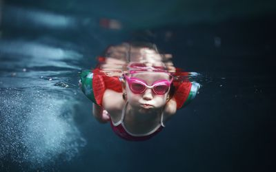 Young girl swimming underwater wearing pink goggles