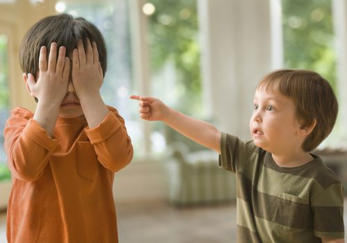 preschool age boy pointing at brother who is covering his eyes