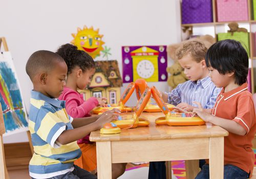 Children playing with toy laptops in class