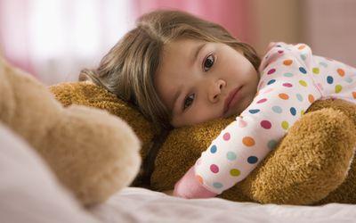 Little girl awake in bed, holding a teddy bear