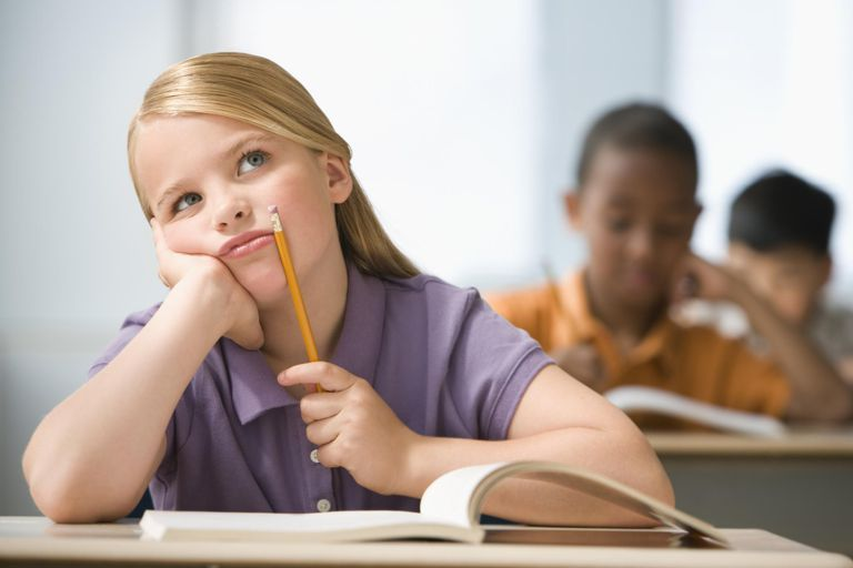 Girl (6-7) sitting in classroom with head in hands, students in background.