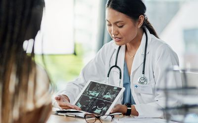 Closeup shot of a doctor showing a patient ultrasound scans on a digital tablet in her office