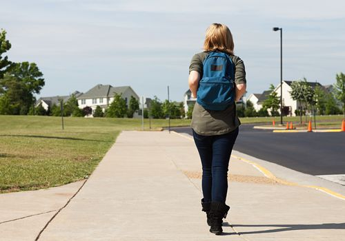 Back of a young teen girl wearing a backpack and walking in school parking lot