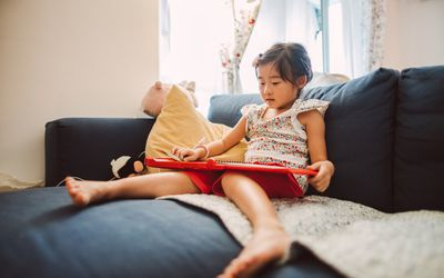 Lovely little girl reading an electronic book on the sofa happily.