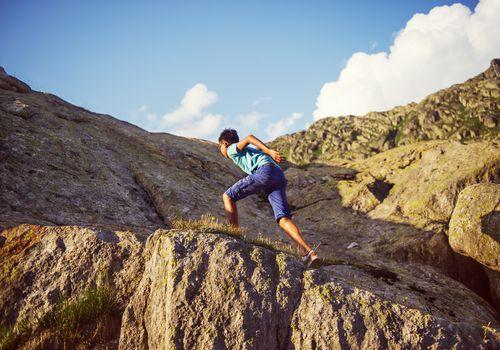 Boy climbing up rocks