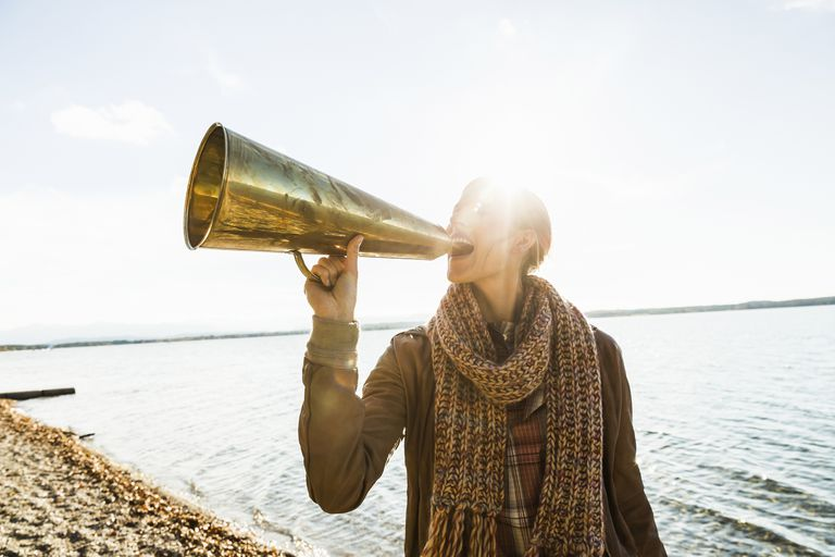 Woman shouting into megaphone by the sea