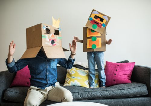 Father and daughter wearing robot costumes at home