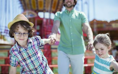 Girl and boy pulling their father in amusement park