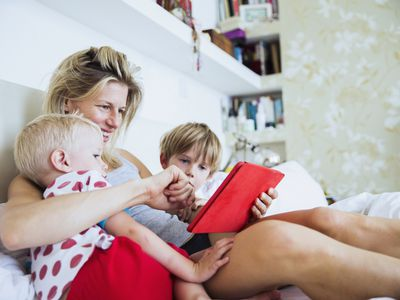Mom reading with her two kids in an apartment