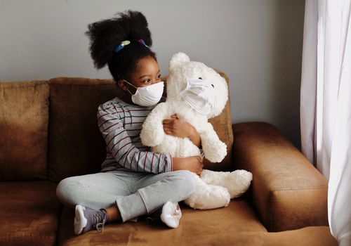 Young girl wearing a mask, holding teddy bear wearing a mask on a couch