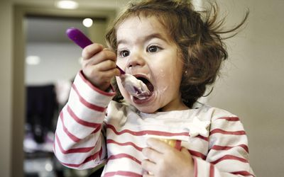 Toddler girl feeding herself yoghurt in a spoon