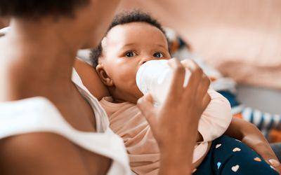 Mother bottle-feeding her infant daughter