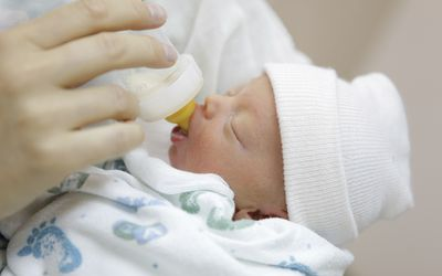 Mother Bottle Feeding Her Premature Baby In The Hospital Nursery