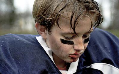 little boy wearing football gear