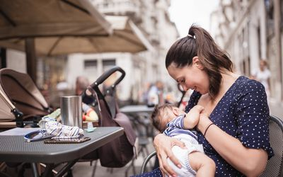 Young mother breastfeeding her baby boy at outdoor cafe