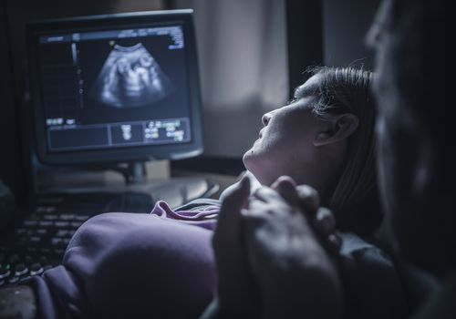 Pregnant couple holding hands during ultrasound