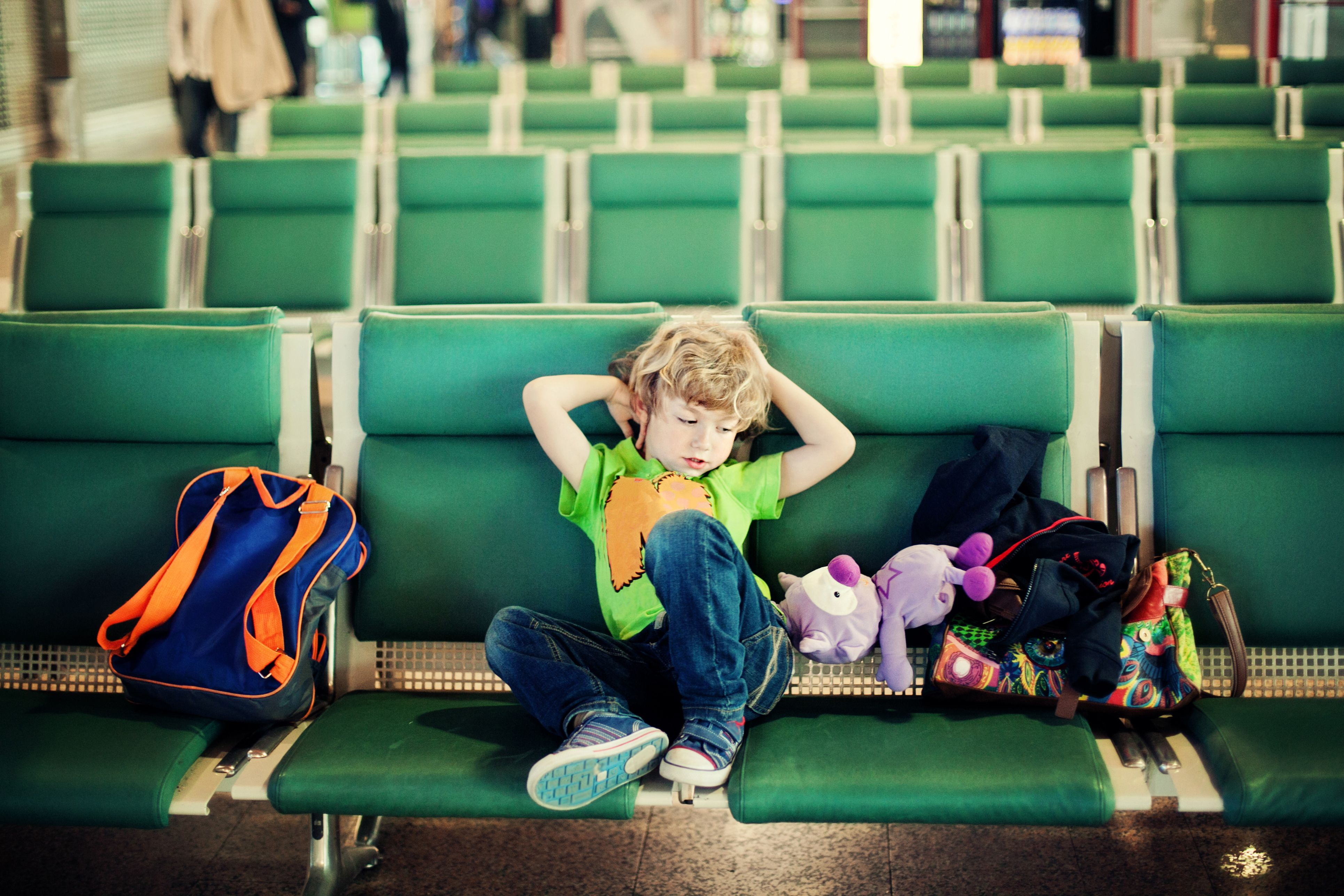 Child lounging on airport chairs