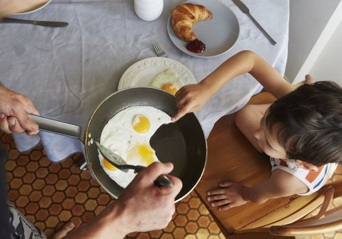 Parent offering child frying pan of sunnyside up eggs at breakfast table