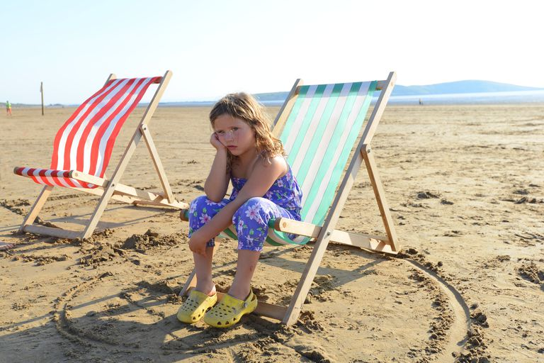 Sulking young girl in beach chair