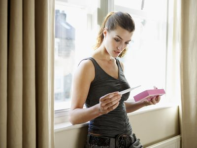 A woman looking at a home pregnancy test