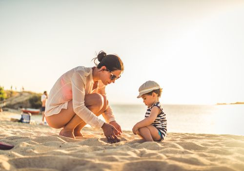 Mother and toddler playing with sand on a beach