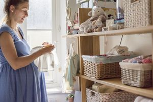 A pregnant woman in a nursery sorting out baby clothes.