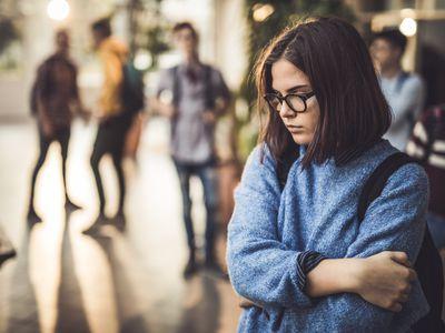 Troubled teen alone in high school hallway