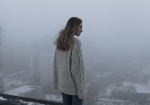 woman wearing a sweater standing amidst pollution