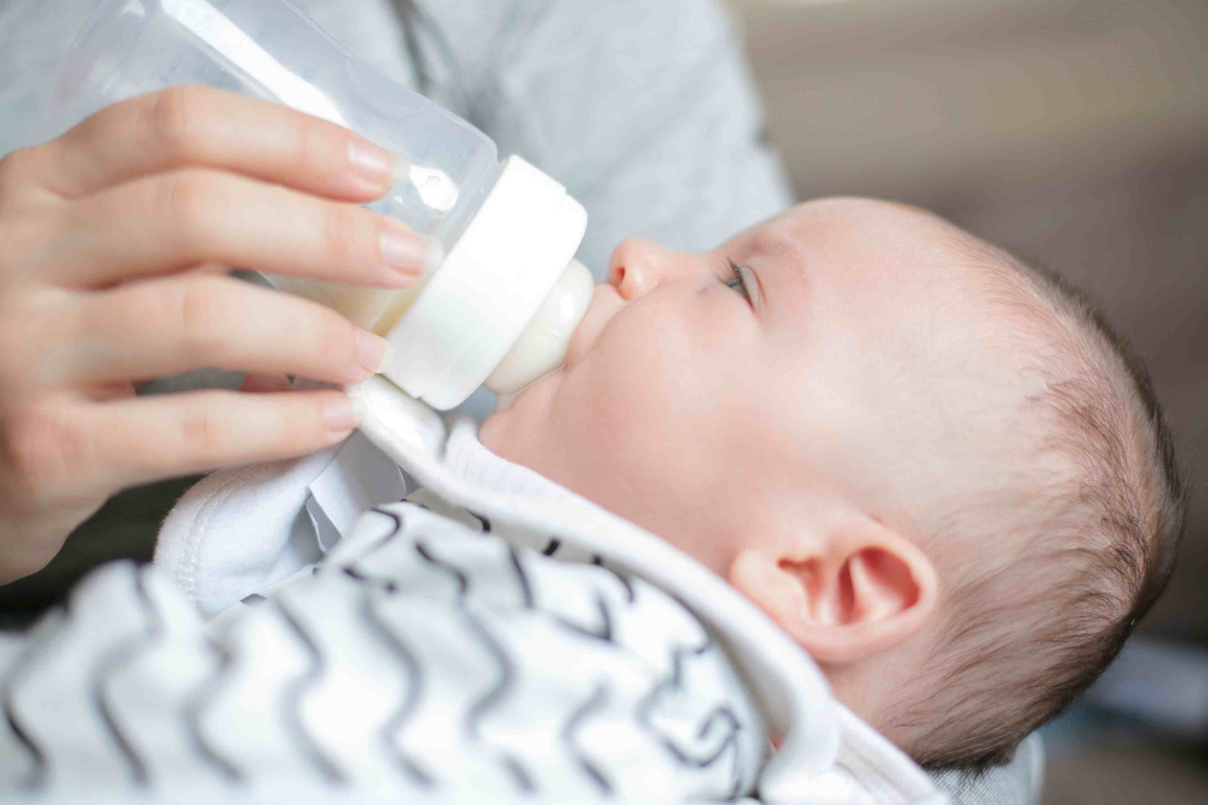 Midsection of mother feeding milk to baby boy with bottle at home