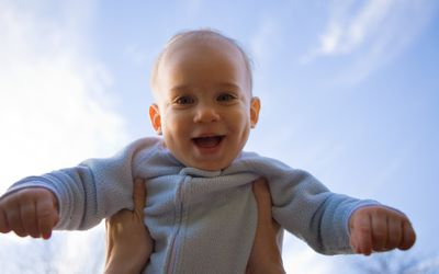 Smiling baby being lifted up to the sky