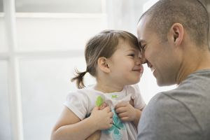 Father and toddler daughter smiling with heads pushed together