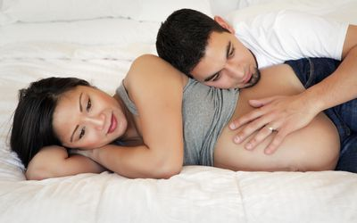 Pregnant woman laying on bed