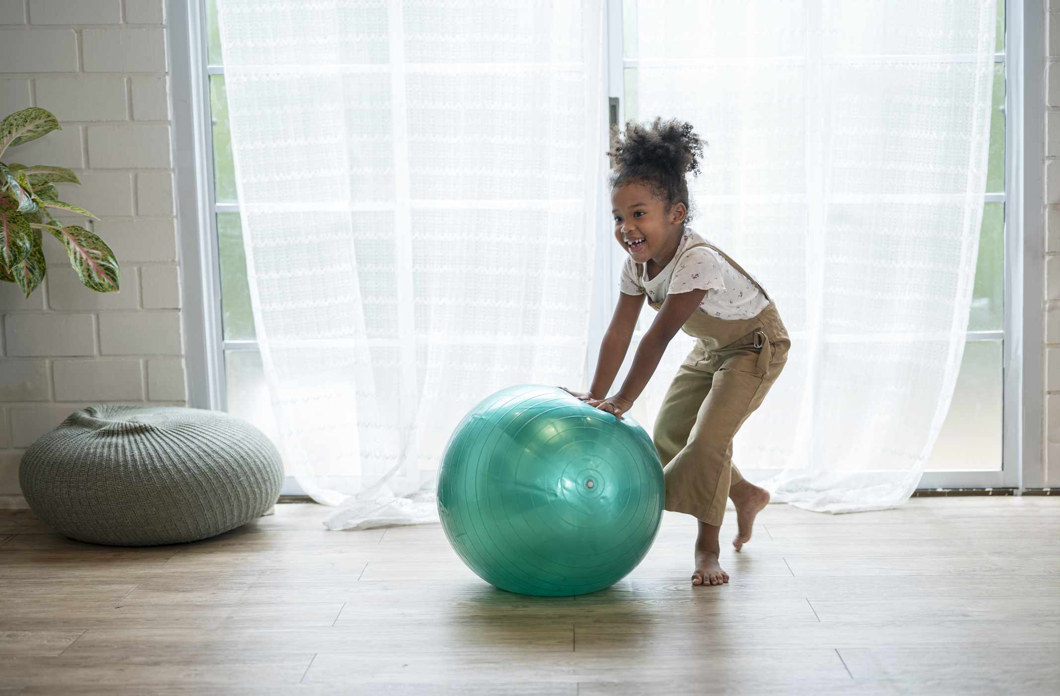 A girl playing with a bright green yoga ball inside