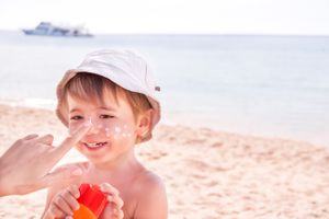 Little boy in a hat on the beach getting sunscreen put on his face.