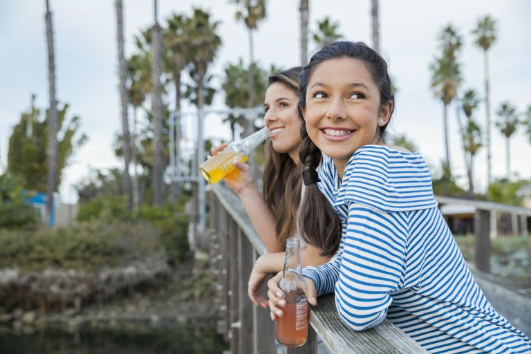 Teenage sisters enjoying a refreshment on a pier