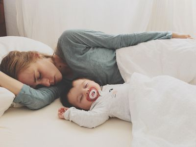 Mom and baby lying in bed together