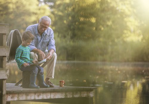 Grandfather and grandson reading on the dock of a lake