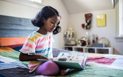 Little girl reading on her bed