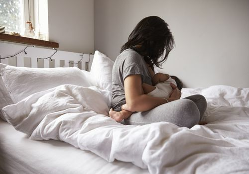 Woman breastfeeding baby while sitting on a bed