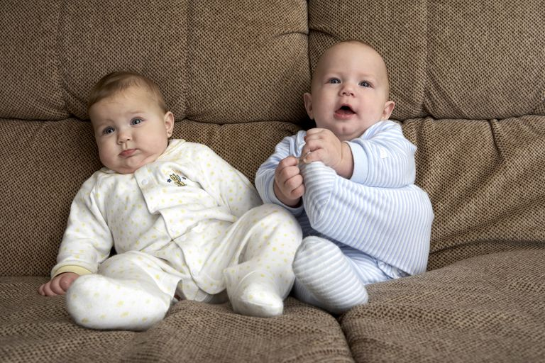 Two babies sitting on a couch