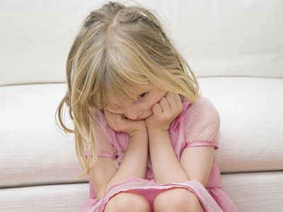 Sad young girl sitting on a couch