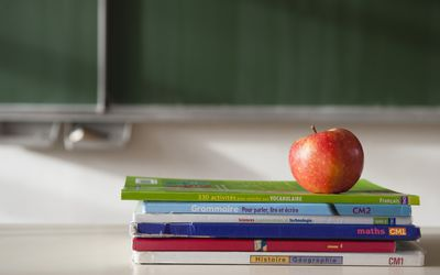 School workbooks and an apple on a teachers desk