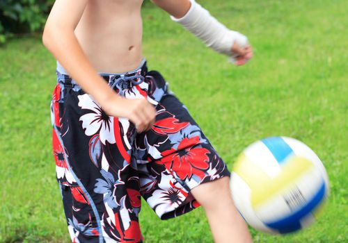 Boy wearing cast on arm kicking a soccer ball